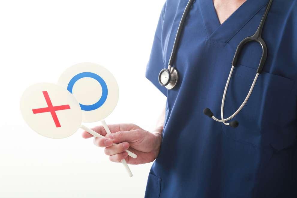 医療職が○と✕の札を持っている